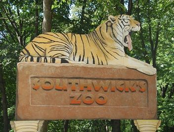Sign for the Southwick Zoo with yawning lion on top.