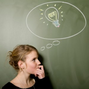 Thinking woman standing in front of chalkboard with a drawn light bulb.