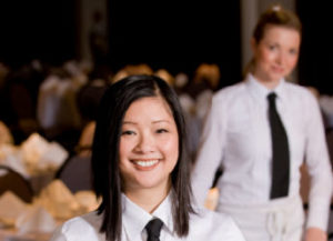 Two smiling female restaurant staff at nice restaurant.