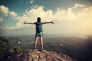 Successful woman hiker open arms hiking on mountain peak.