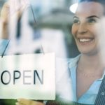 Woman holding open sign in cafe.