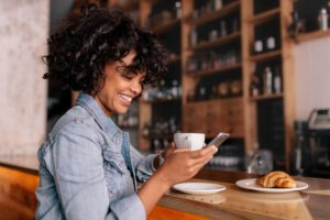 Smiling woman using smart phone in a modern cafe.