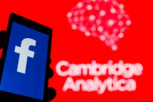 Smartphone in hand with logo of popular social network Facebook. Cambridge Analytica emblem in background.