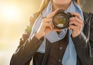 Picture of a photographer holding a digital camera pointed at viewer.