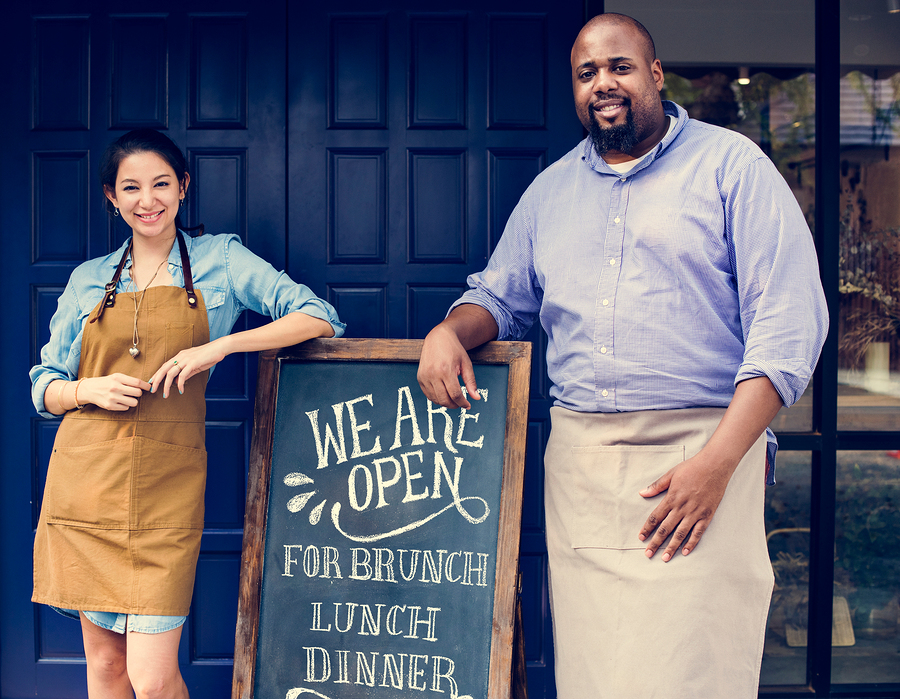 "Cheerful restaurant owners standing with ""we are open"" blackboard."