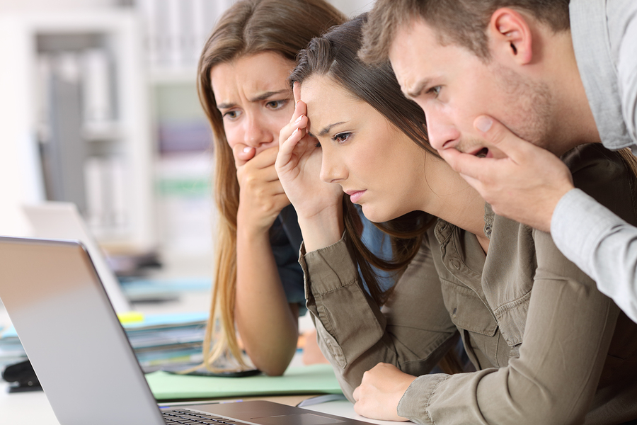 Three employees looking at a laptop unhappily.