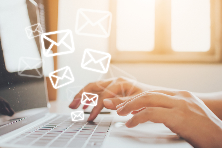 Person typing on keyboard with images of email icons floating above, represending newsletters or emails.