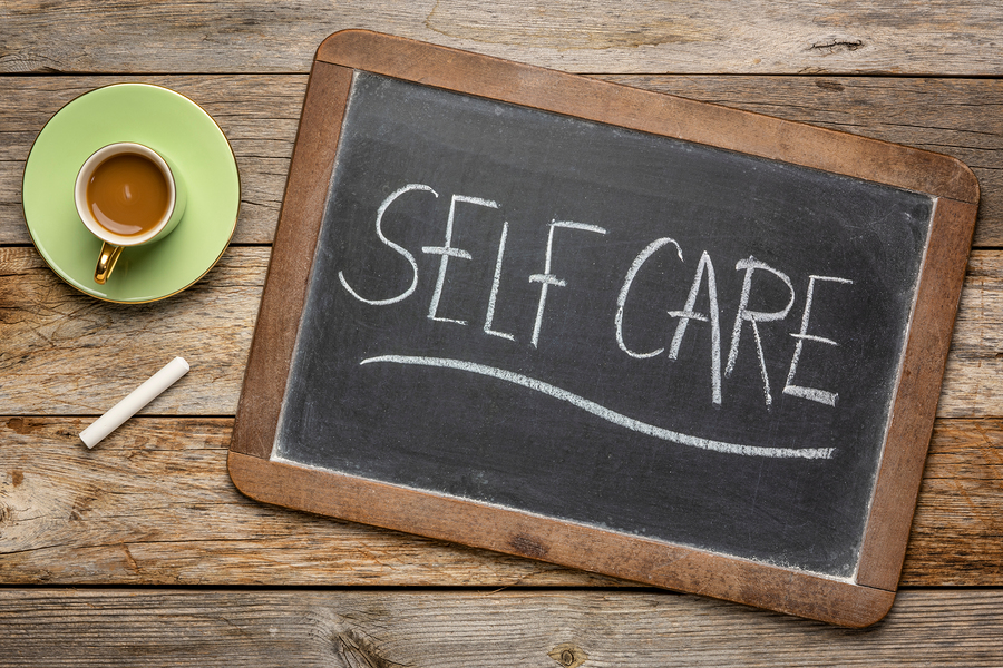 A picture of a chalkboard with self-care written on it next to a cup of coffee on top of a rustic, wooden table.