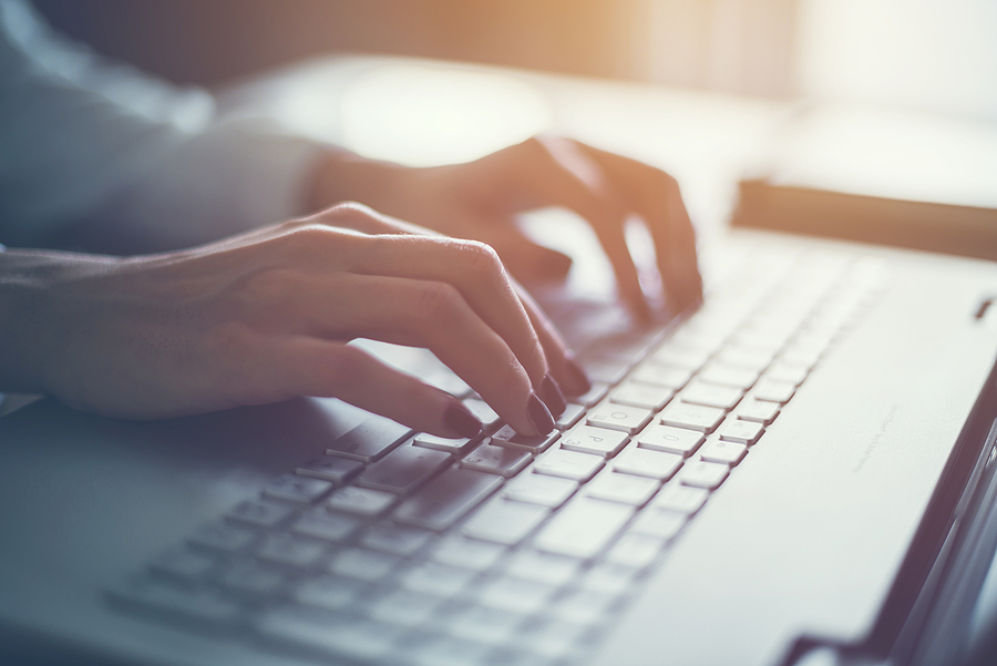 Woman's hands typing on a laptop keyboard in subdued lighting.
