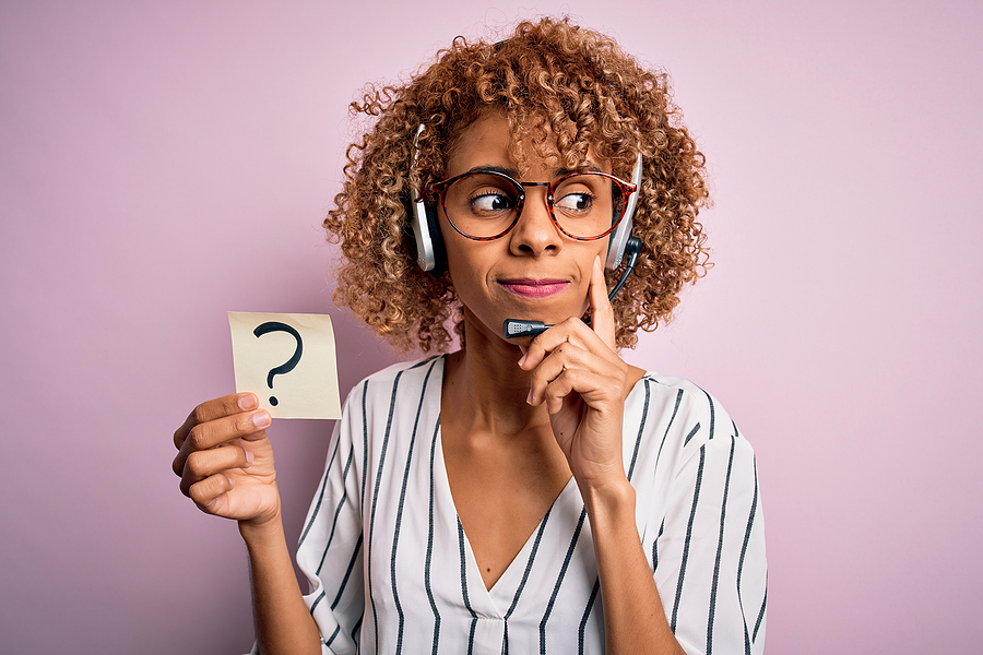 A women wearing a headset holding a post-it note with a question mark on it, indicating the important of asking questions as a professional