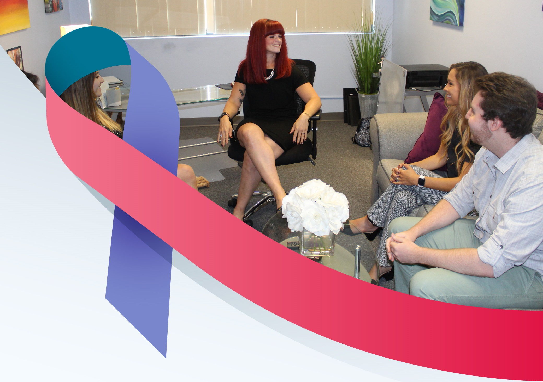 Julia Becker Collins sitting in her office with interns with Thyroid Cancer Awareness Ribbon in foreground.
