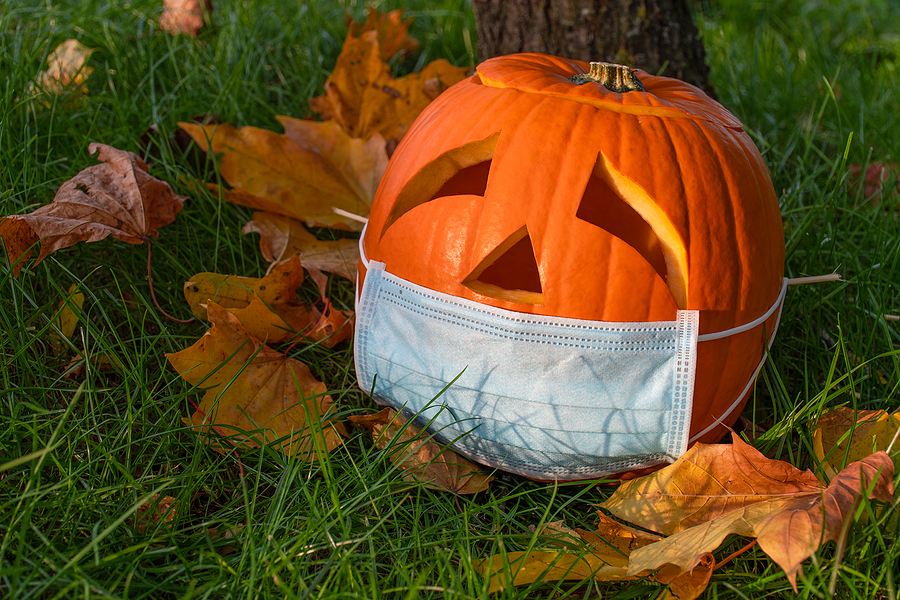 A Halloween Jack-O-Lantern wearing a surgeon's mask atop fallen leaves in green grass in October.