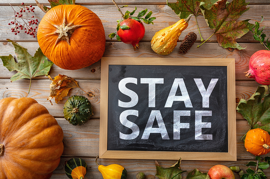 "A rustic wooden table topped with an assortment of Thanksgiving Day vegetables such as squash and pumpkins next to a sign that reads, ""Stay Safe."""