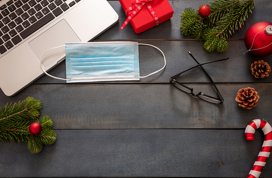 A dark, wooden table with a small, wrapped gift, a pair of glasses, pine branches and pinecones, a laptop, and a face mask on top.