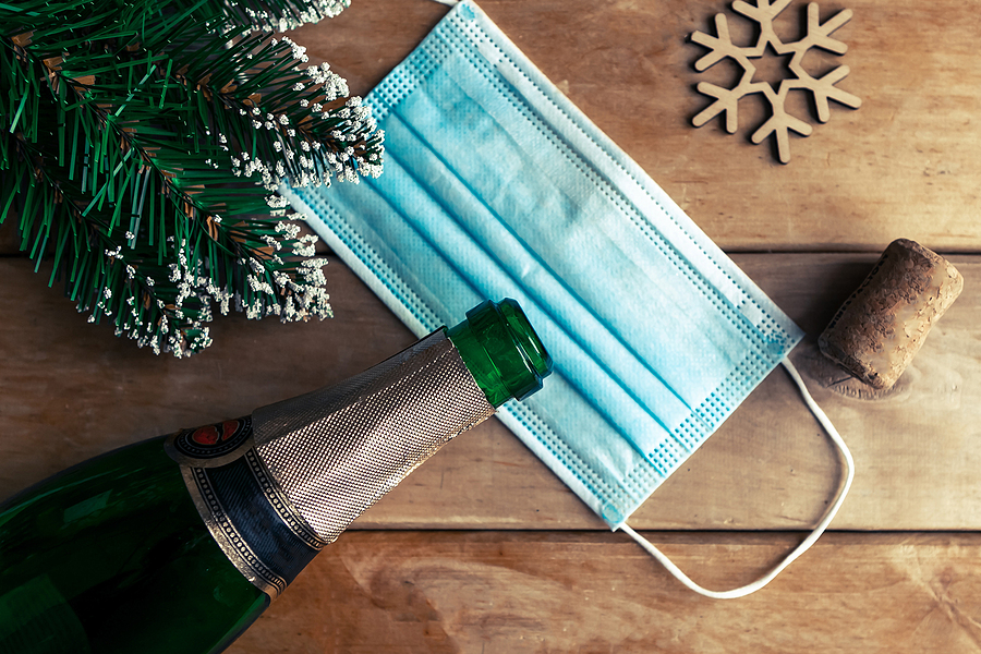 Frosted pine needles, a wooden snowflake, and a popped bottle of champagne lying over a face mask atop a wooden table.