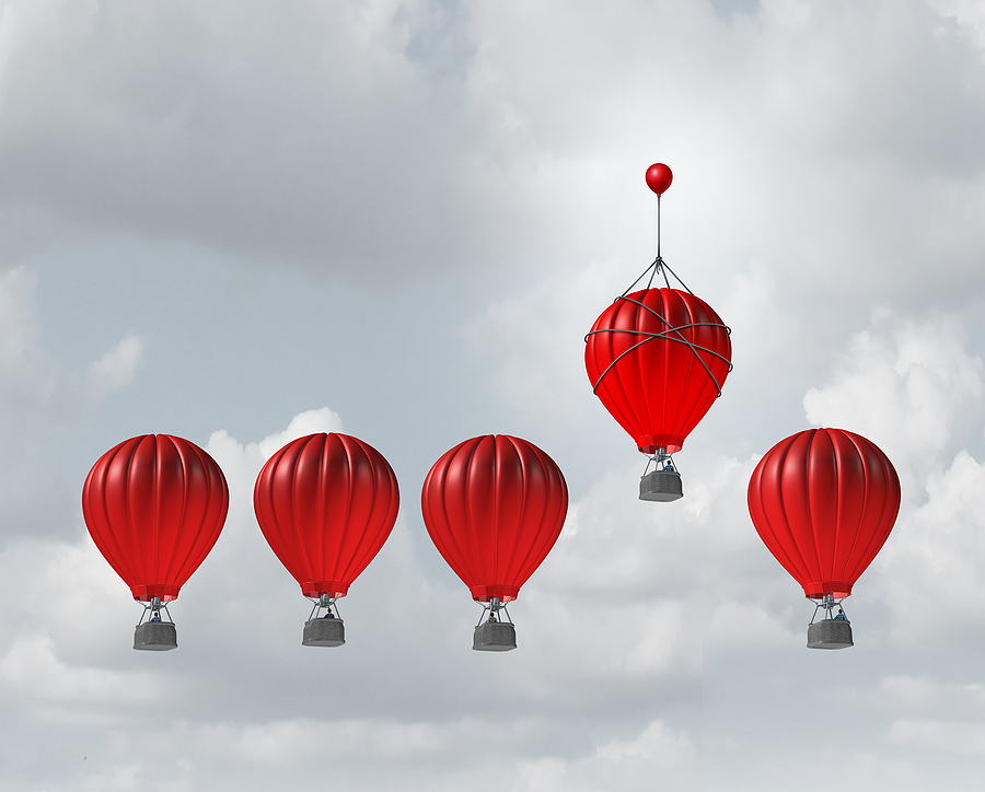 Five red hot air balloons in a cloudy gray sky, with one hot air balloon slight higher than the others with the help of a smaller balloon tied to the top. A picture meant to show the competitive edge of cross-selling vs. upselling.