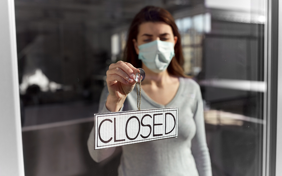 Woman in face mask hangs closed sign on door of shuttered business.