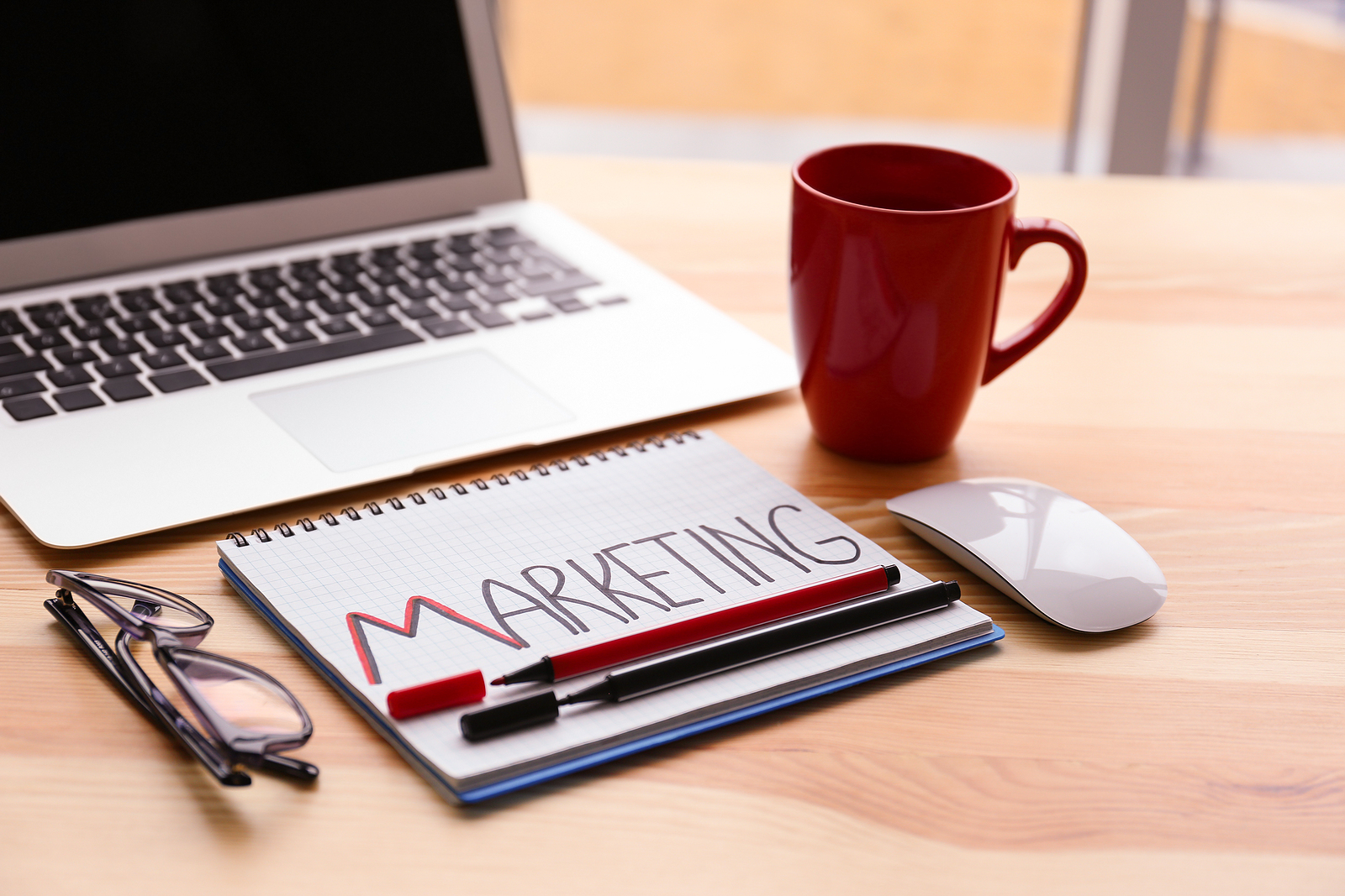 "A notebook with ""Marketing"" written on it next to a pair of glasses, a coffee mug, a computer mouse, and a laptop on top of a desk."