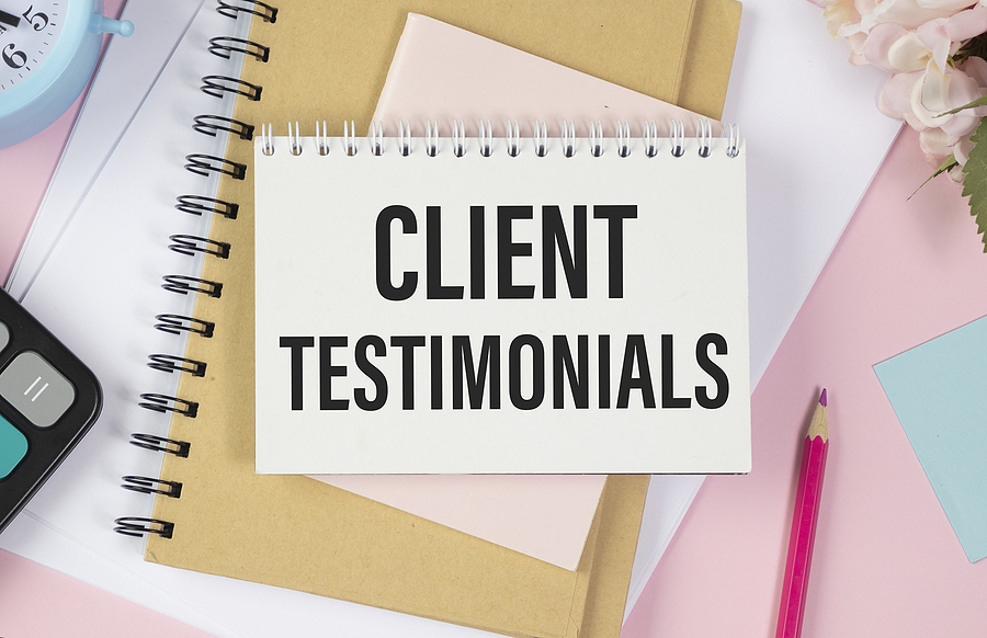 """""""Client Testimonials"""" written on a notepad on top of a pick desk cluttered with notebooks."""
