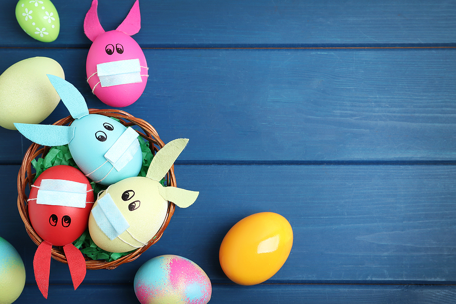 Painted Easter eggs in a basket with rabbit ears and mini masks on top of a blue table, meant to signify COVID-19 regulations in April
