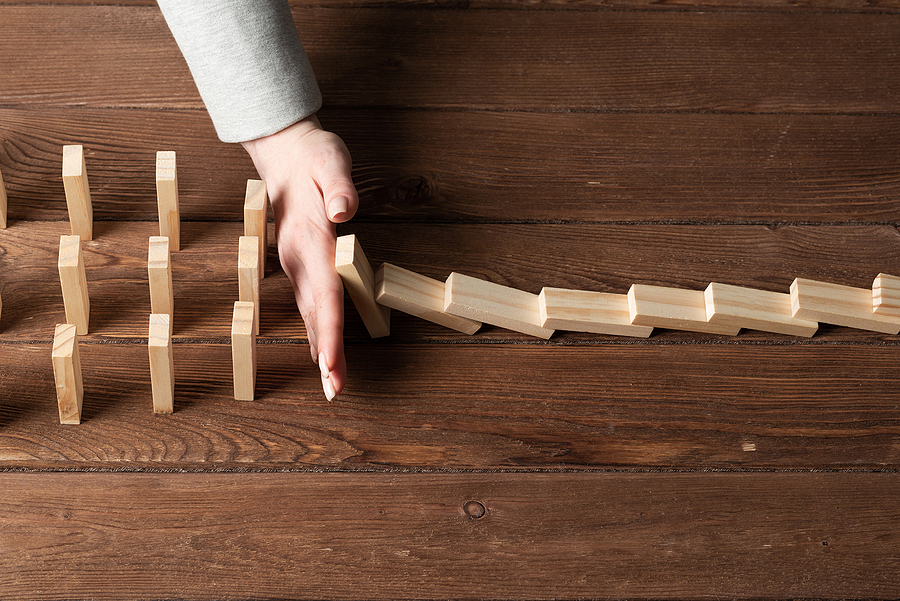 A business woman using her hand to some a line of dominoes from tipping over a large grouping of dominoes on a wooden desk, meant to portray crisis management for businesses