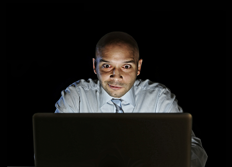 Business owner or marketer staring red-eyed at laptop, representing obsessing over a single analytics metric.