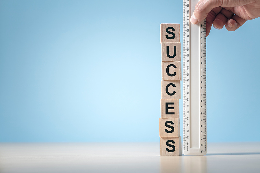 """A plastic ruler measure the height of a tower of blocks that spell out """"success"""""""