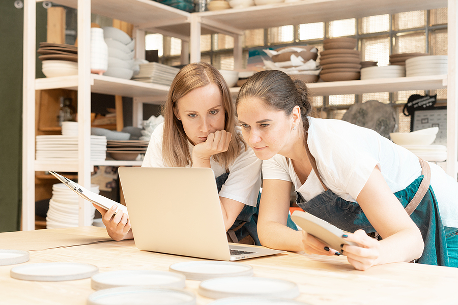 Two female artisans surrounded by pottery on shelves staring at a laptop.