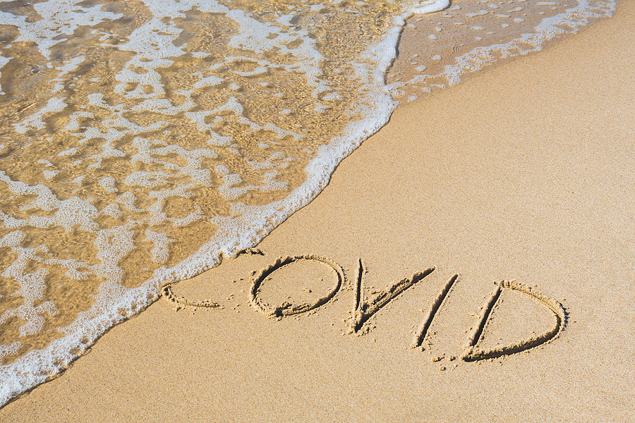 """The word """"COVID"""" written in the sand on the beach with a small wave washing it away."""