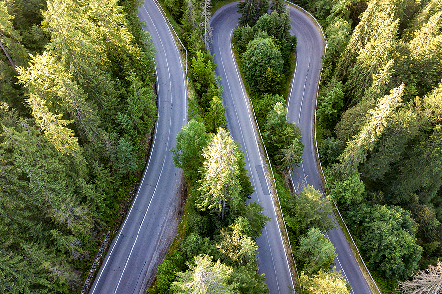 Aerial view of winding road in high mountain pass trough dense trees, meant to illustrate mapping your customer journey.