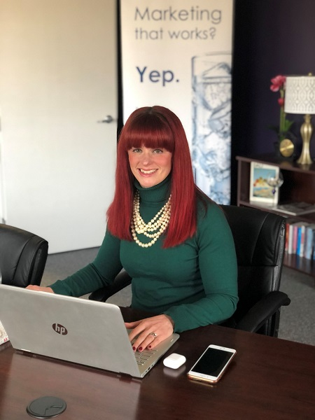 COO Julia Becker Collins at the Vision Advertising Office on her laptop.