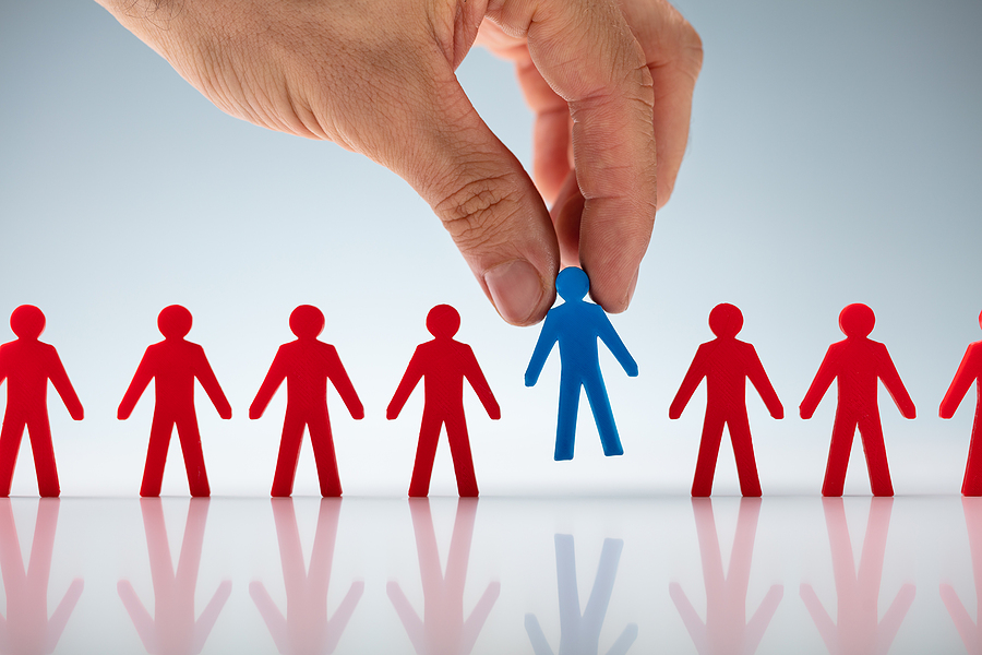 A hand reaching down and picking up a blue figurine out of a lineup of red figurines meant to signify your ideal client profile