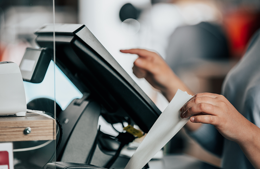 Saleswoman printing out a receipt from a machine next to a touchscreen register.